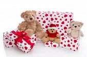 Teddy Bears Surrounded By Christmas Gift Boxes On White Background