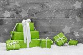 stock photo of coupon  - Green Christmas presents with snow on grey wooden background for a greeting card or coupon voucher - JPG
