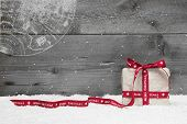 White Christmas Present With Long Ribbon, Snow On Grey Wooden Background