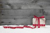 White Gift Box With Red Long Ribbon And Bow On Grey Wooden Background