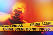 stock photo of flashing  - Crime Scene Do Not Cross Yellow Headband Tape and Orange flashing and revolving light - JPG
