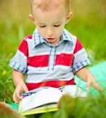 Little boy is reading book while sitting on green grass outdoors