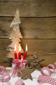 Advent: Four Red Burning Candles With Christmas Decoration  Ribbons, Wooden Stars And Tree On Wooden