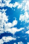 Abstract background of beautiful curly and sparse clouds like whitecaps over light bright blue sky i