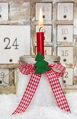 One Red Advent Candle With A Red Checkered Bow For Christmas