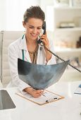 Smiling Doctor Woman With Fluorography Talking Phone