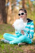 Smiling Girl In Sportswear With Cotton Candy In Summer Park.