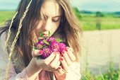 Beauty Of Nature. Young Beautiful Girl Smelling Meadow Clover Flowers