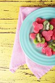 Slices of watermelon in plate on napkin on wooden background