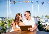 love, dating, people and food concept - smiling couple wearing sunglasses holding menu and looking t