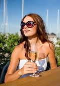 people, summer, drinks and holidays concept - smiling young woman wearing sunglasses drinking champa