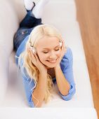 technology, music and happiness concept - smiling young woman in headphones at home