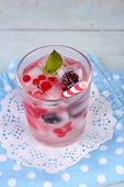 Cold cocktail with forest berries, frozen in ice cubes on color wooden background