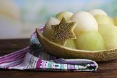 Melon in melon peel on napkin on wooden table on natural background