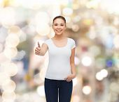 advertising, holidays, gesture and people concept - smiling young woman in blank white t-shirt showi