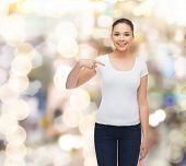 gesture, holidays, advertising and concept - smiling young woman in blank white t-shirt pointing fin