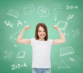advertising, gesture, school, education and people - smiling little girl in white blank t-shirt with
