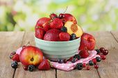 Peaches and berries in bowl on table on natural background