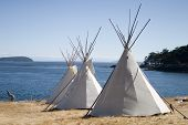 foto of tipi  - Three teepees (aka tipis) are lined up in a row in front of water. These teepees are used at a summer camp. Teepees were one form of traditional shelter used by native americans.