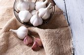 Fresh garlic in basket, on wooden background