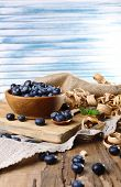 Wooden bowl of blueberries on cutting board on sacking napkin on wooden table on light background