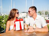 love, dating, people and holidays concept - smiling couple wearing sunglasses sitting with gift box,