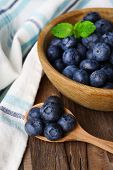 Wooden bowl of blueberries on napkin on wooden background closeup