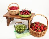 Fresh berries in baskets on white wall background