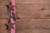 Wooden Christmas Stars On Checkered Ribbon On Wooden Background For A Greeting Card