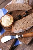 Fresh toast with homemade butter and blackcurrant jam on wooden background