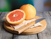 Ripe grapefruits on wooden board, on bright background