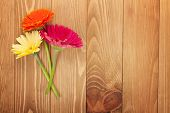 Three colorful gerbera flowers on wooden table with copy space