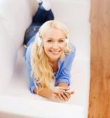 home, leisure, technology and internet concept - smiling woman with smartphone and headphones lying