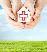 healthcare, medicine and charity concept - male and female hands holding white paper house with red cross sign