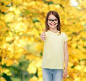 education, school and vision concept - smiling cute little girl in black eyeglasses showing thumbs u