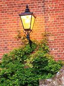 Illuminated Lantern Against Brick Wall