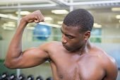 Close up of a shirtless young muscular man flexing muscles in gym