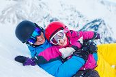 Father and child in ski equipment playing in snow