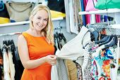 woman choosing dress during shopping at garments clothing shop