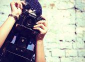Retro photographer. Modern urban girl has fun with vintage photo camera outdoor near grunge wall, image toned.