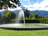 Water Fountain With Mountain Background In A Bright Sunny Day