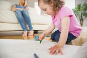 Little girl drawing in the living room with mother sitting behind at home