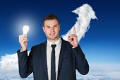 Composite image of businessman holding light bulb and pointing against cloud arrow