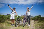 Full length portrait of athletic couple mountain biking