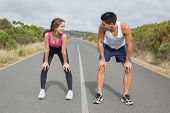 Fit young couple running on the open road together