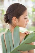 Beautiful brunette posing with palm leaf at the health spa