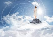Thinking businesswoman against mountain peak through the clouds
