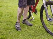 Closeup lowsection of muddy cyclist with bike outdoors