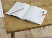 Open notebook with pencil and pencil sharpener on table, elevated view