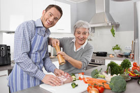 picture of older men  - Young man and older woman cooking together in the kitchen and have fun - JPG
